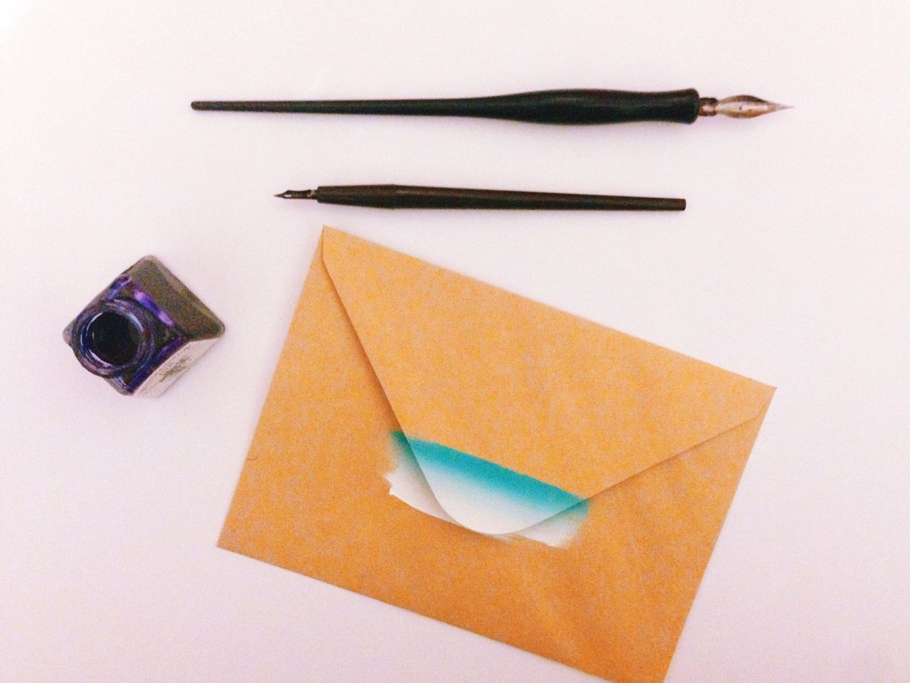 High angle view of envelop with ink well and pen