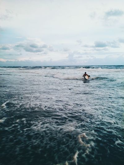 Man with surfboard walking in sea against cloudy sky