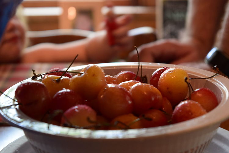 Close-up of wet cherries in bowl on table
