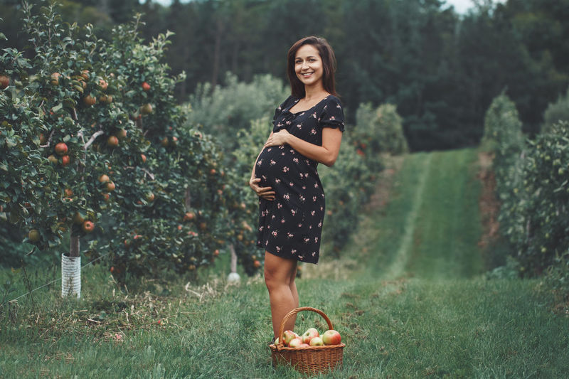 Portrait of pregnant woman standing at farm