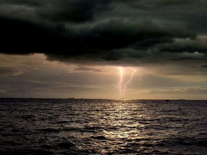 Thunderstorm On Sea Against Sky During Sunset