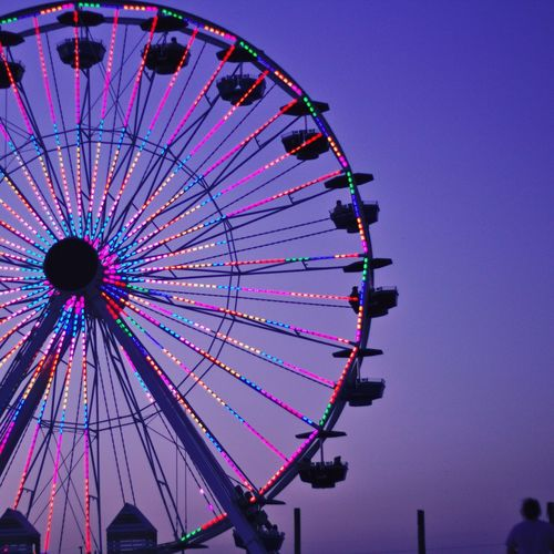 Low angle view of illuminated ferris wheel against clear sky at dusk