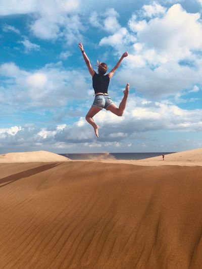 Rear view of woman jumping over sand in desert against sky