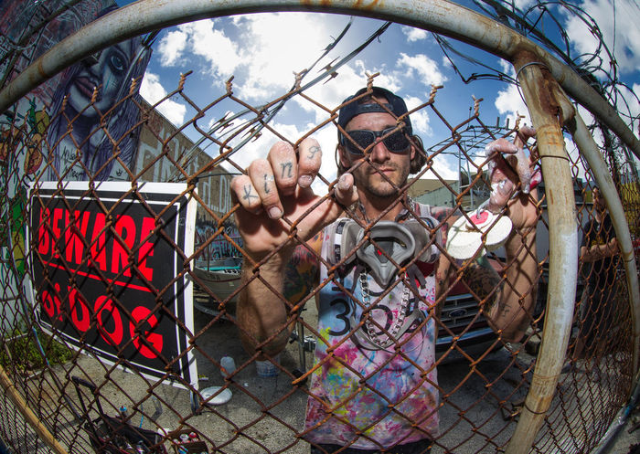 one half of 2square Street Artist Boogierez Casual Clothing Fence Fisheye Street Photography Illvisuals Lifestyle Photography Looking At Camera Male Model One Person Outdoors Paint On Hands Rezones Urban Wynwoodwalls
