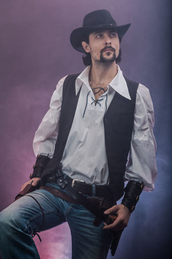 Handsome young man. This is an American cowboy. A vow to a white shirt, brown waistcoat and blue jeans. Black shoes on the feet. Carries a shtyapa, on a belt two pistols. The hair is of medium length; on the face is a beard and mustache. Authentic photo. Culture of America. Cowboy Wild West America American Gun National Authentic Moments Lifestyles Lifestyle One Person Candid Authentic Smoke Hat Jeans Facial Hair Beard Mustache Males  Standing Three Quarter Length Young Adult Handsome Looking Clothing