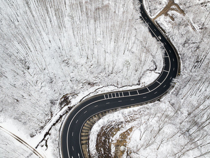 Winding road through the forest, from high mountain pass, in winter time. aerial view by drone