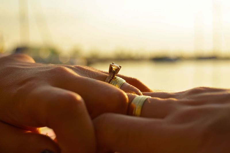 Cropped Hands Of Couple Wearing Wedding Rings