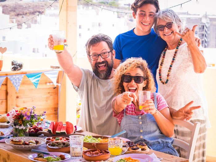 Portrait of happy family with food and drinks at restaurant