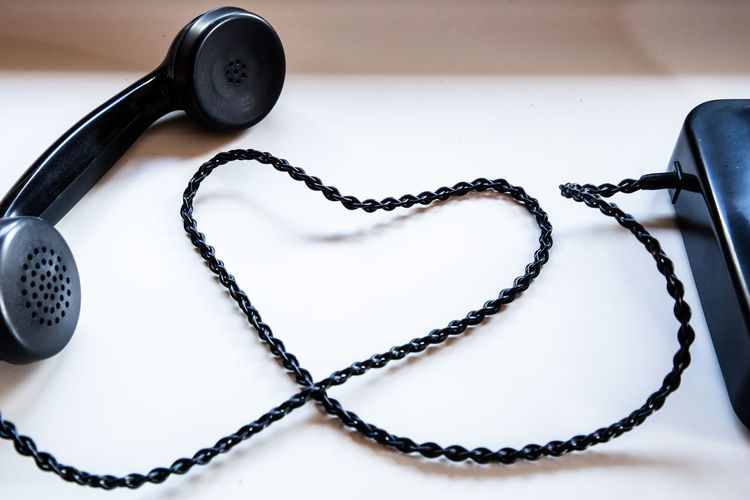 High angle view of telephone receiver making heart shape on table