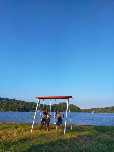 People sitting on grass at lake against clear blue sky