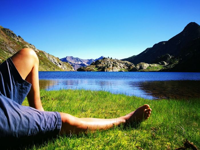 Low section of woman relaxing on grass by lake against sky