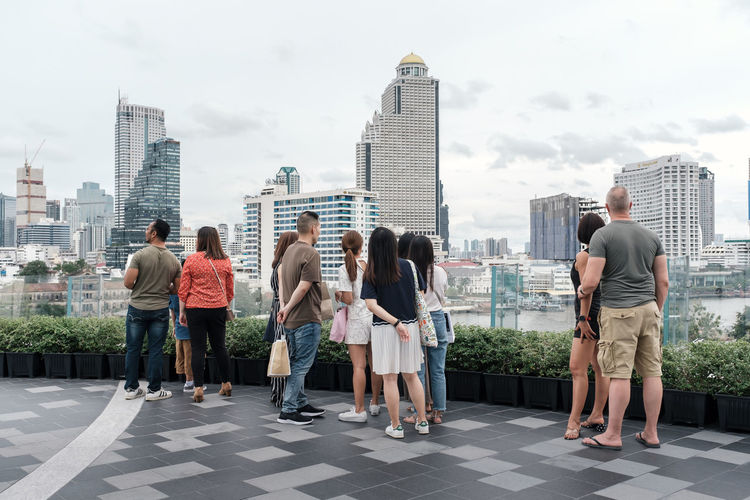 Rear view of people against buildings in city