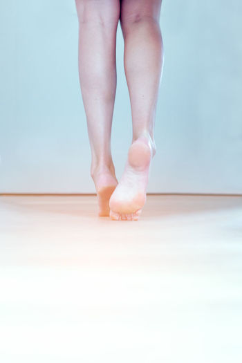 Low Section Of Woman Tiptoeing On Floor