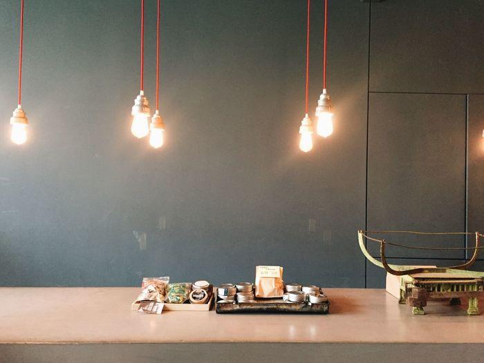 Illuminated light bulbs hanging over table