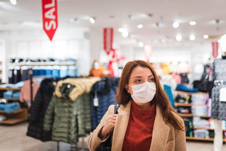 Woman wearing mask looking away at shopping mall