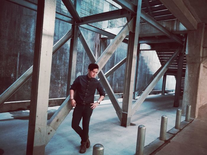 Full length of young man standing by metallic structure