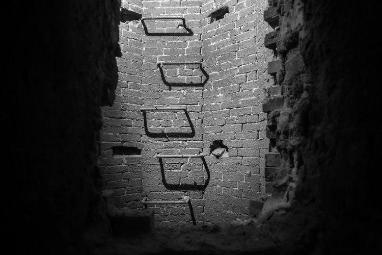Metal steps on wall inside of manhole