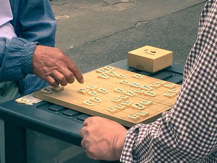 Midsection of male friends playing shogi while sitting outdoors
