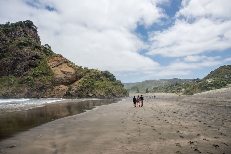 Auckland, New Zealand-December 17,2016: Stunning black sand Piha Beach on an overcast day in Auckland, New Zealand Auckland Green Holiday Lion Rock Tasman Sea Tourist Travel Tree Vacations Beach Black Sand Beach Geology Leisure Activity Mountain Nature New Zealand Piha Real People Sand Scenics - Nature Sea Travel Destinations Volcanic Landscape Volcano Water