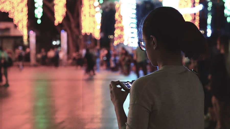 Woman Using Mobile Phone In Illuminated City