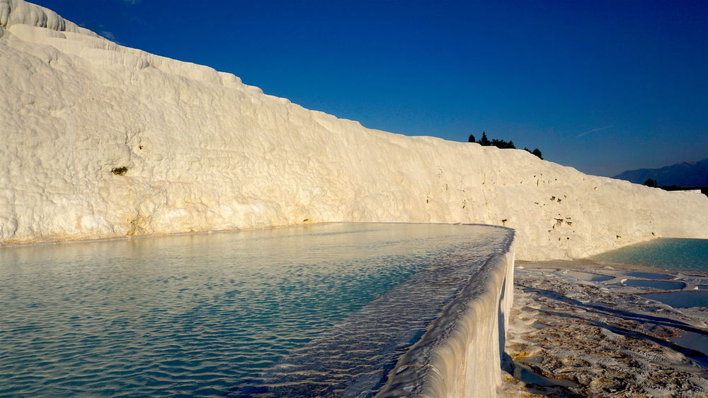 White Calcium travertines and pools as a heritage geological langscape of Pamukkale Pamukkale Cotton Castles Pamukkale/Turkey Beauty In Nature Clear Sky Day Mountain Nature No People Outdoors Pamukkale Scenics Sky Tranquil Scene Tranquility Water