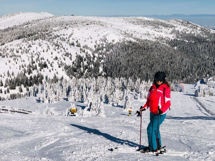 Woman skier on the slope with view of snowcapped mountains ahead on a day with clear blue sky Landscape Blue Sky Pine Tree Coniferous Tree Forest Ski Resort  Resort Slope Adult Woman Skier Sport Winter Full Length Real People Leisure Activity Snow Sunlight Cold Temperature Day Winter Sport Mountain One Person Mountain Range Ski-wear Ski Holiday Nature Beauty In Nature Scenics - Nature Lifestyles