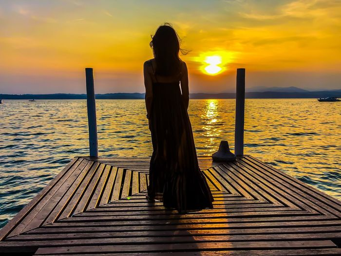 Rear view of woman standing on pier by sea against sky during sunset