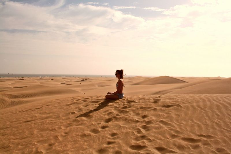 Side view of young woman sitting on sand against cloudy sky