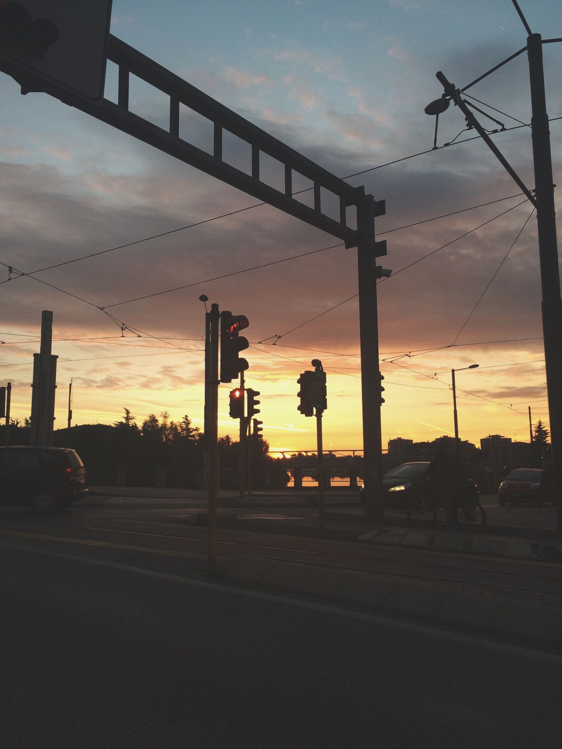 sunset, sky, built structure, architecture, transportation, street light, cloud - sky, silhouette, building exterior, street, road, cloud, orange color, the way forward, power line, electricity pylon, outdoors, connection, dusk, city