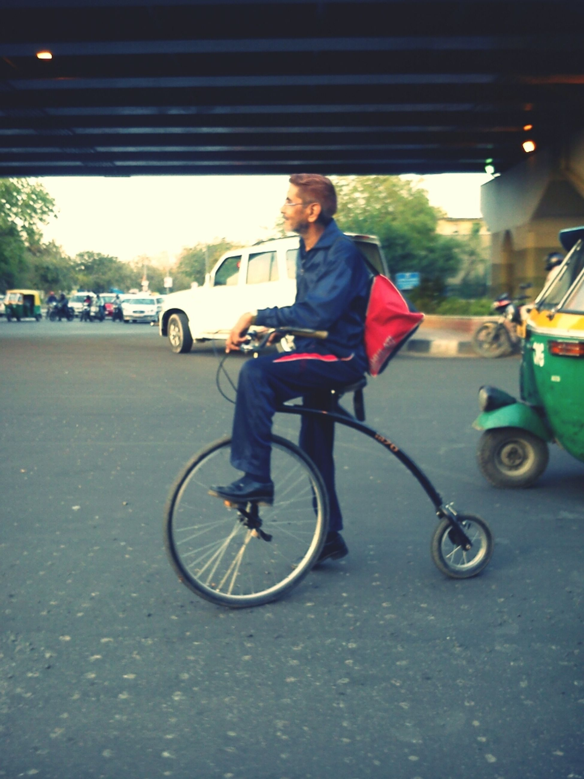 transportation, mode of transport, land vehicle, full length, lifestyles, car, leisure activity, casual clothing, bicycle, street, riding, road, travel, person, on the move, young adult, front view, motion