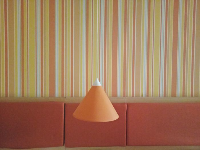Close-up of electric lamp hanging against sofa and wall