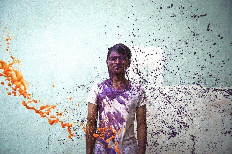 Man standing amidst splashing paints against wall