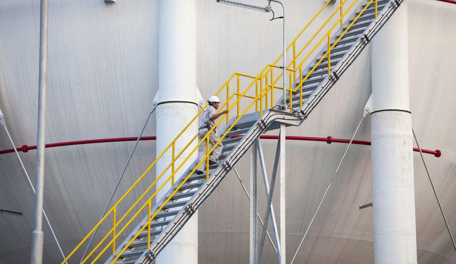 Man walking up stairs next to storage tank