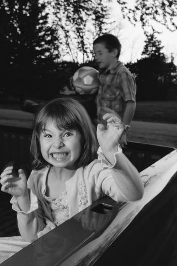 Portrait Of Playful Girl With Brother In Pick-Up Truck At Park