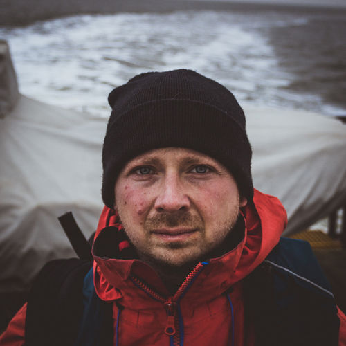 Close-up portrait of man wearing knit hat on boat in sea