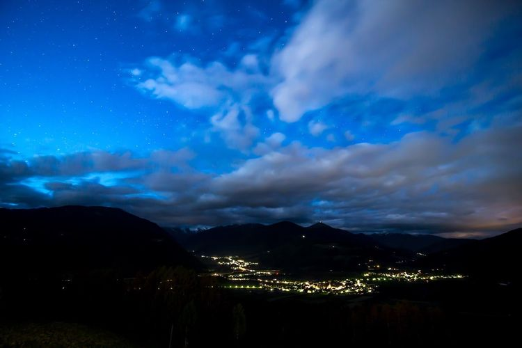 Scenic view of landscape against cloudy sky at night