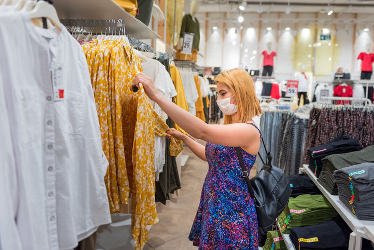 Side view of woman wearing mask looking at clothes at store
