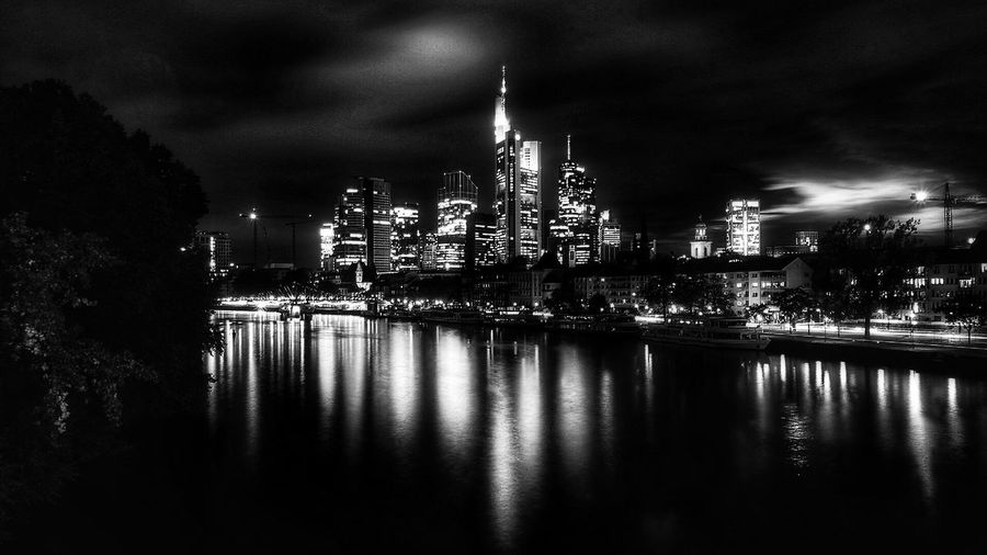 River By Illuminated Cityscape Against Sky