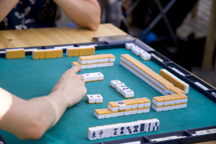 Playing the national Japanese Mahjong table game Board Games Games Japanese  Japanese Culture Board Game Board Game Party Close-up Game Human Body Part Human Hand Indoors  Japanese Game Mahjong Mahjong Session Mahjong Tiles Multi Colored Real People Skill