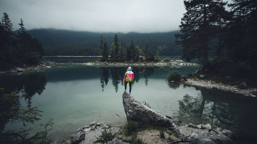 One Person Rear View Outdoors Water Eibsee See Alpen Zugspitze Germany Reflection Tree Mountain Fog Moody Sky Non-urban Scene Real People Hiking Traveling Roaming Nature Jacket Standing Full Length View Clear Water
