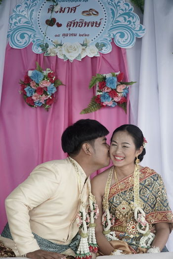 Young couple kissing against curtain