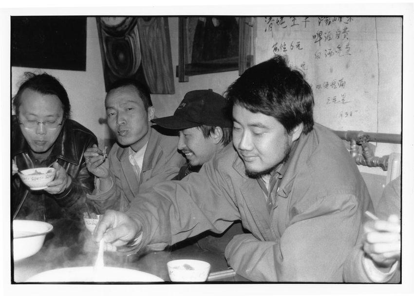 山东人老三2000年在宋庄的大兴庄开设了三元里餐厅,宋庄的艺术家在这里只需花三元即可吃饱喝好。当时宋庄阳盛阴衰,光棍居多,自然都懒得做饭。这里正好也成了聚会交流的好去处,在其它村子居住的艺术家也常来此,一度人气兴旺。老三好酒,印象最深的是院子的角落里堆了好多二锅头的空塑料桶。只是不知何故,三元里经营不到一年就关门大吉。后听说老三好东西都留着自己吃,给艺术家饭菜里的硬货却越来越少。时日一久,艺术家都用脚投票了。后老三离开宋庄,回到山东老家。几年后老三在山东老家自杀,但应该与三元里无关。 图为在三元里就餐的艺术家,左起:石立峰、小飞、片山、尹坤。身后的墙上是当日的菜谱。2000年 12820764 1613 10909308