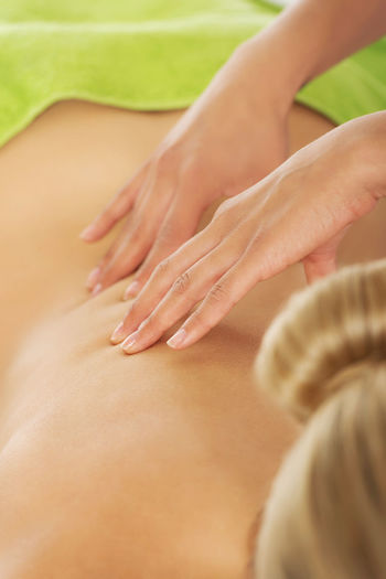 Cropped hands therapist massaging woman in spa