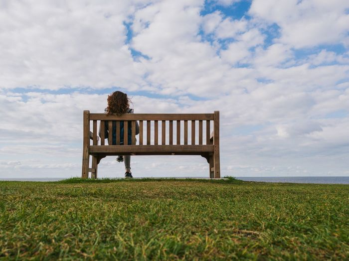 Rear view of woman sitting on bench against sky