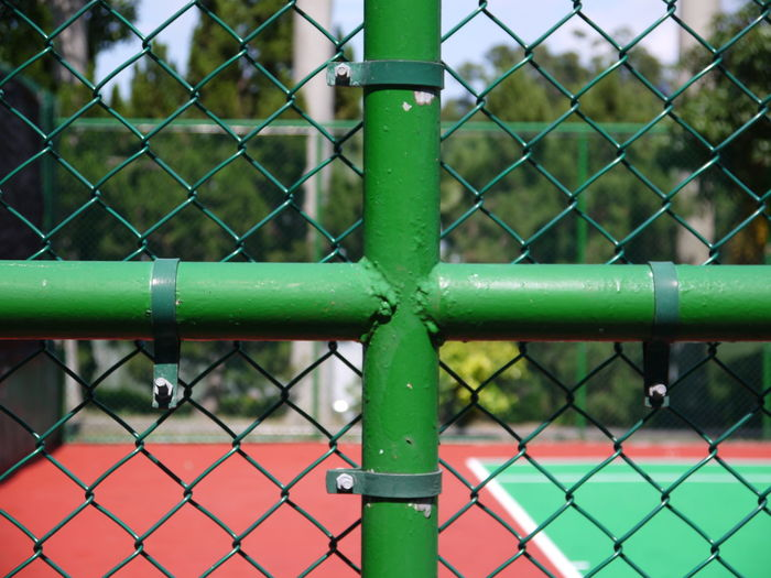 Close-up of plus shape pipe on chainlink fence against tennis court
