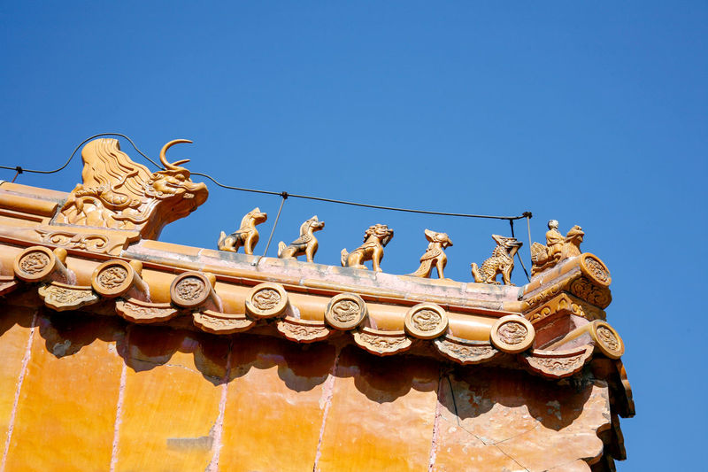 Roof of traditional chinese temple with orange ceramic tiles and an ornate red stone gable Sky Clear Sky Architecture Low Angle View Art And Craft Blue Sculpture Representation Built Structure Day Animal Representation Nature Copy Space Creativity Craft Building Exterior No People Sunlight History Statue Outdoors Ornate Carving Chiness China Traditional Culture Architecture Dragon Roof Ceramic Tiles Gable Rooftop
