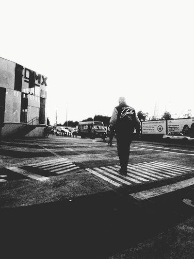 Rear view of man walking on street against clear sky
