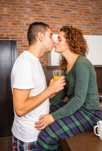 Portrait of loving young couple kissing while having breakfast on the home kitchen Fresh Thirties Relaxing 30s Coffee Orange Juice Drink Food Morning Husband Family Wife Portrait People Indoors  House Lovers Cheerful Girl Boyfriend Handsome Happiness Affection Two Adult Girlfriend Smiling Attractive Romance Lifestyle Female Young Caucasian Male Together Relationship Breakfast Kitchen Home Man Woman Happy Embracing Passion Kissing Kiss Couple Romantic Love