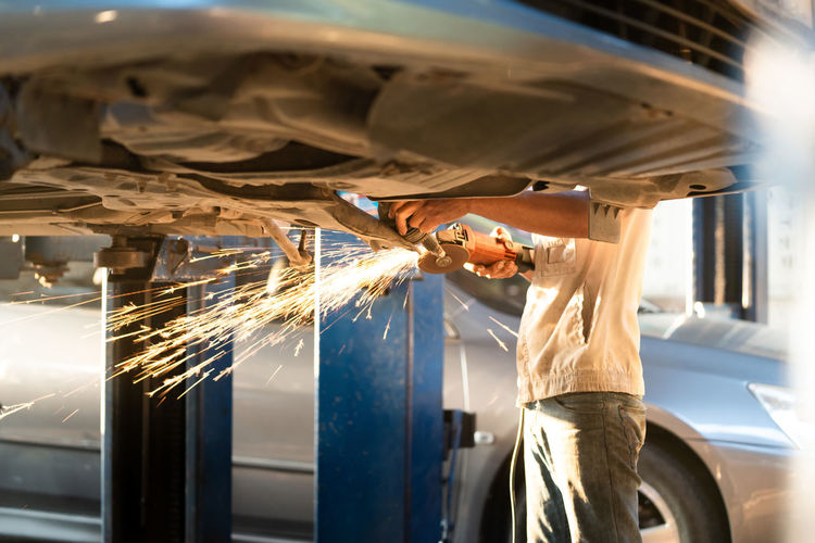 Midsection of mechanic working in auto repair shop