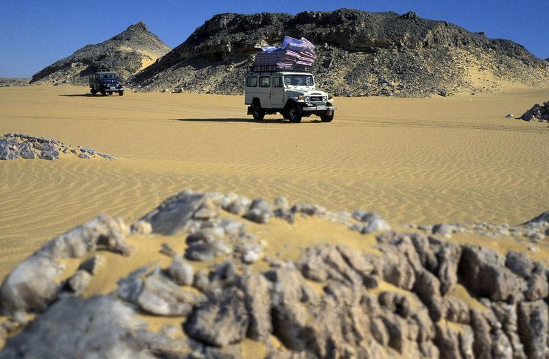 Land Vehicles On Desert Landscape